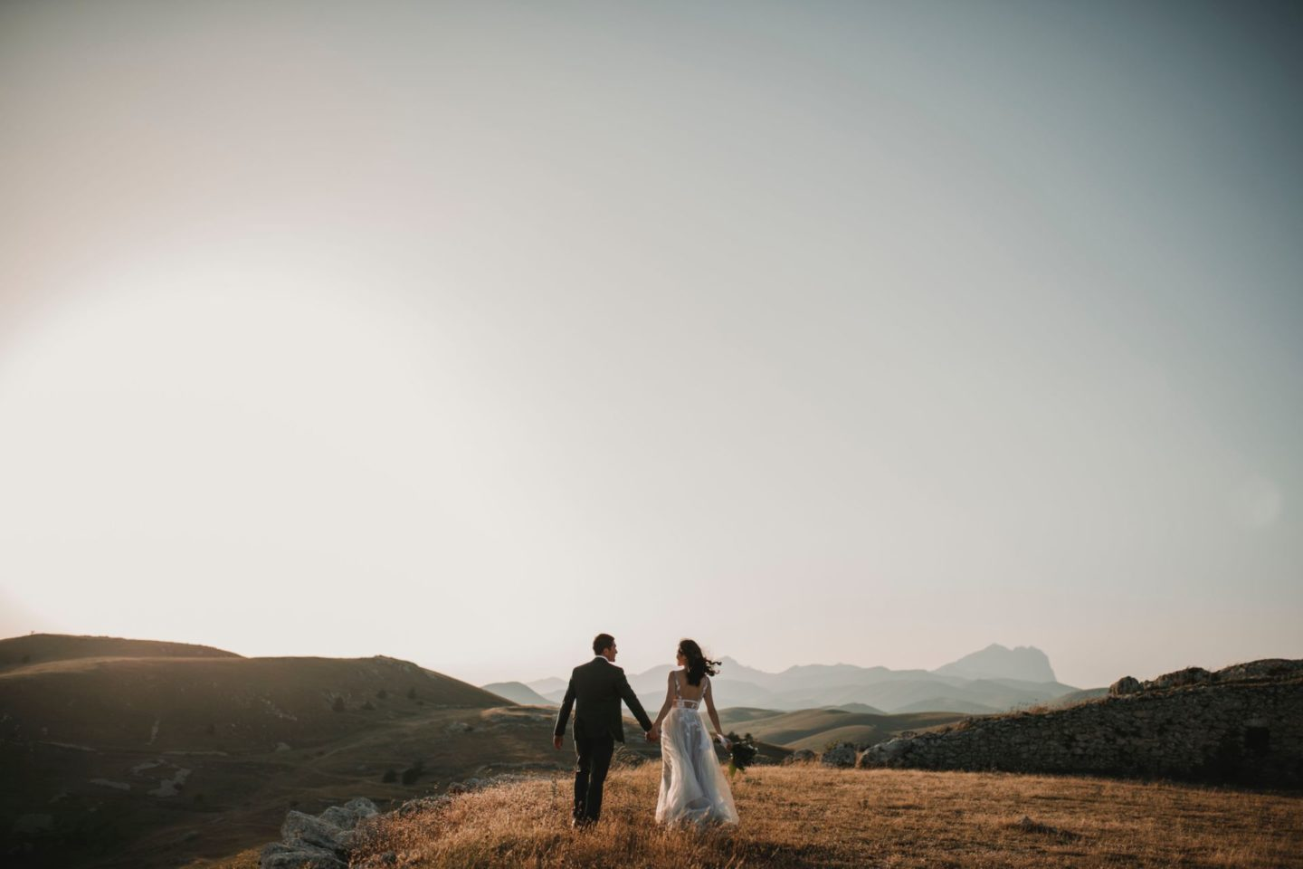 newly wed couple walking away from the camera in a field